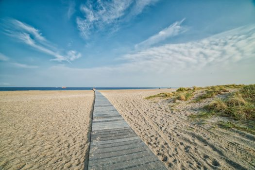 Amager Strand romantic wooden pathway or boardwalk on the beach leading to a calm Baltic Sea. Few people walk in the distance conveying relax, realisation concept. Way or path to success illustration